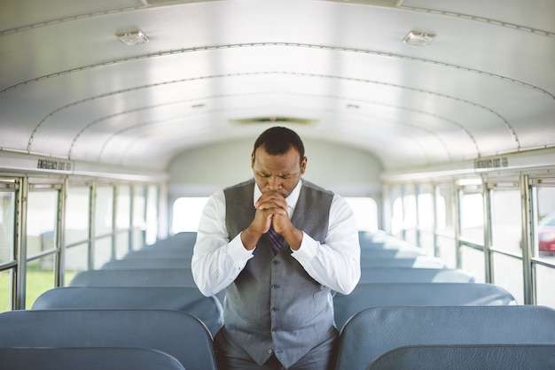 Einsamer afroamerikanischer mann in einem formellen outfit, der tagsüber im bus betet