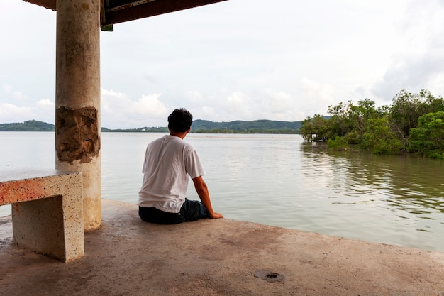 Einsamer asiatischer mann, der allein auf einem pier am tag des schlechten wetters sitzt