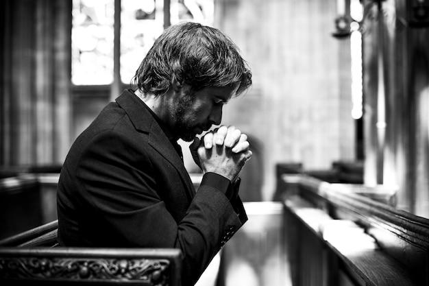 Einsamer christlicher mann, der in der kirche betet