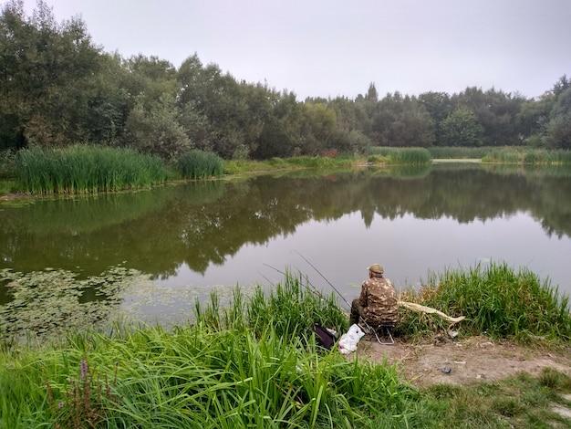 Einsamer fischer auf einem see im sommer