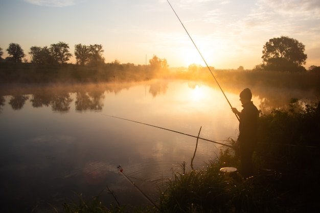Einsamer fischer, der am frühen morgen kurz nach goldenem sonnenaufgang am nebligen see angelt.