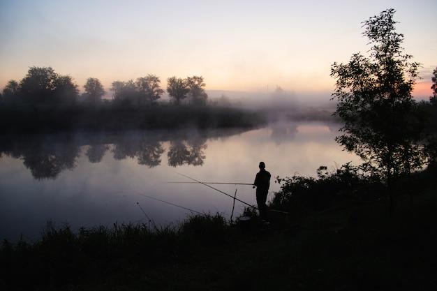 Einsamer fischer, der am frühen morgen kurz vor sonnenaufgang an einem see angelt.