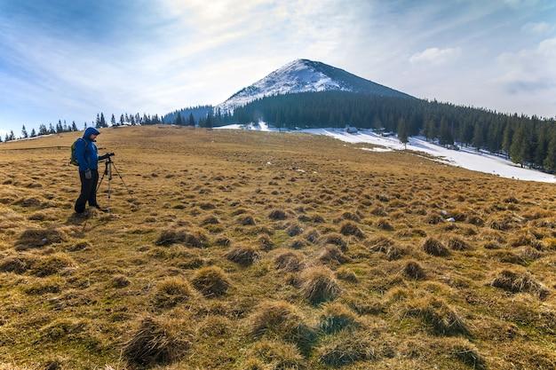 Einsamer fotograf in den bergen mit einer kamera