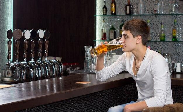 Einsamer junger mann, der allein in der kneipe am ende der bar trinkt