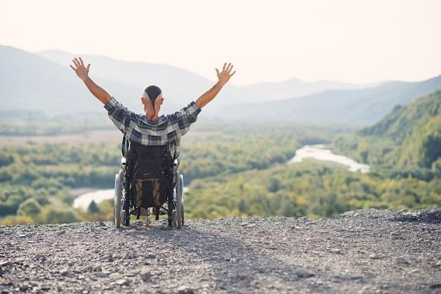 Einsamer junger mann im rollstuhl hob die hände und freute sich über seinen sieg am berg. menschen mit behinderungen reisen.