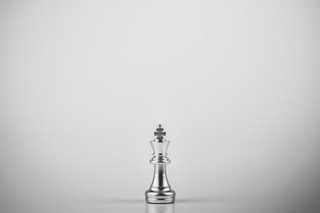 Einsamer königschach, der auf weißem hintergrund steht.