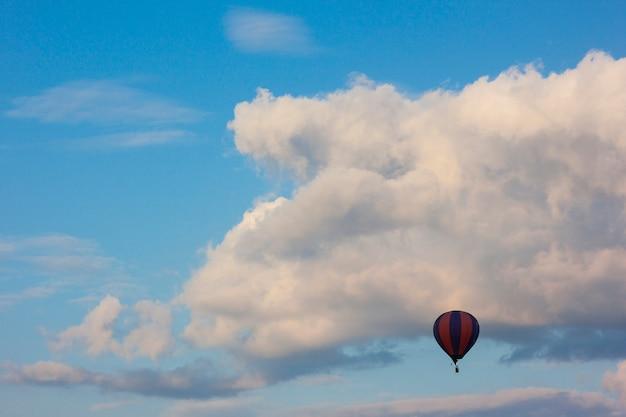 Einsamer luftballon, der vor weißen geschwollenen wolken fliegt