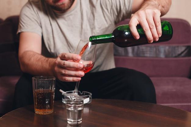 Einsamer mann, der alkohol trinkt