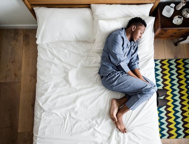 Einsamer mann, der alleine auf dem bett schläft