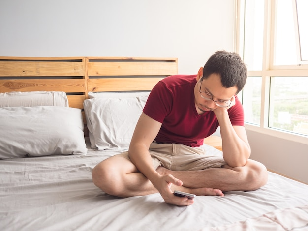 Einsamer nicht-sozialer asiatischer mann mit seinem smartphone in seiner schlafzimmerwohnung.