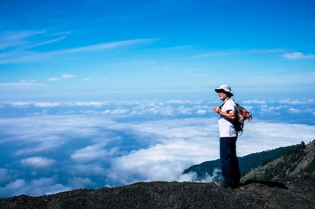 Einsamer pensionierter erwachsener weißer haarmann, der während eines trekking-reiseabenteuers mit seinem rucksack steht und die wunderschöne landschaft des wolkenmeeres vor sich sieht. erstaunliche natur