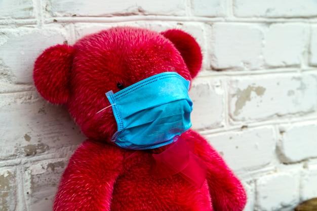 Einsamer roter teddybär in einer medizinischen schutzmaske auf gelbem grund mit atemmasken. coronavirus-covid-19-präventionskonzept.