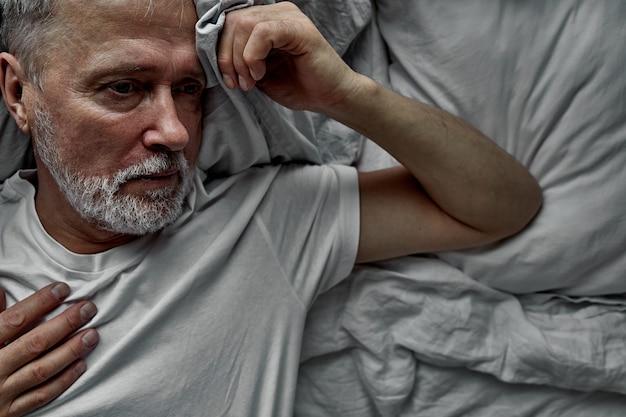 Einsamer senior, der auf bett in einem krankenhaus liegt, krankenhausaufenthaltskonzept. an krankheit einsamkeit leiden