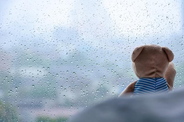Einsamer teddy bear, der auf bett sitzt und heraus dem fenster am regnerischen tag betrachtet.
