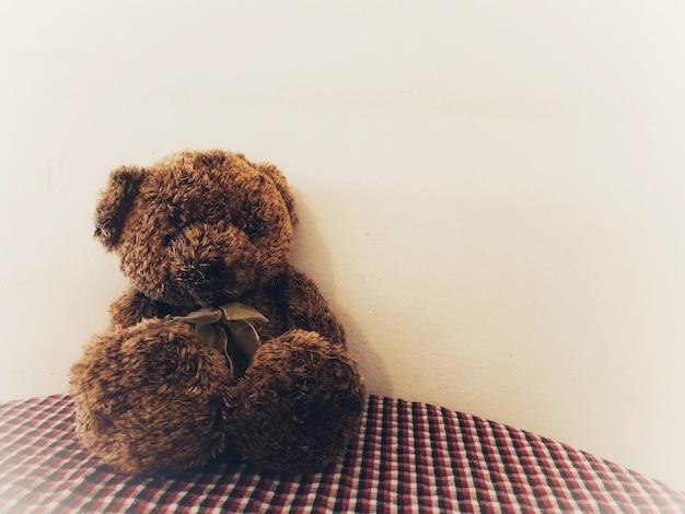 Einsamer teddybär, der auf jemand wartet, um mit hoffnung zu umarmen.