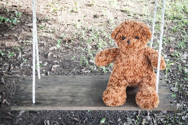 Einsamer teddybär, der auf schwingen sitzt. alleine fühlen. lieblingspuppe