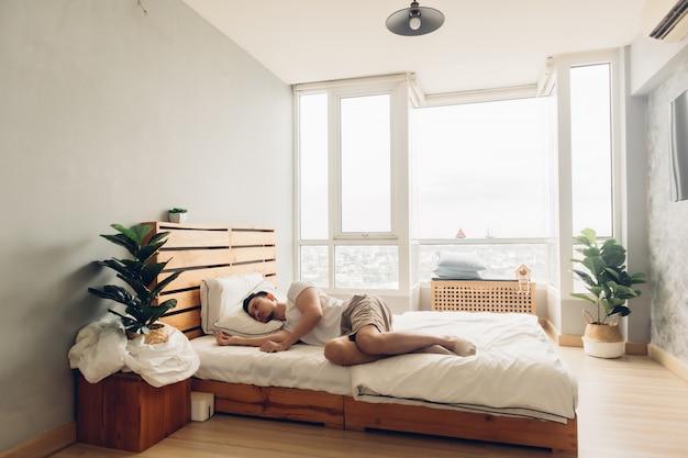 Einsamer und depressiver mann in seinem schlafzimmer in der wohnung.