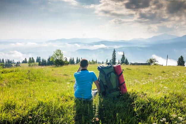 Einsamer wanderertourist, der mounain ansicht am sonnigen sommertag enjoing ist