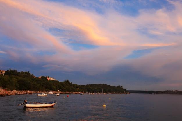 Einsames boot im sonnenuntergang mit dramatischem himmel. sonnenuntergang auf hoher see mit einem fischereifahrzeug am horizont.