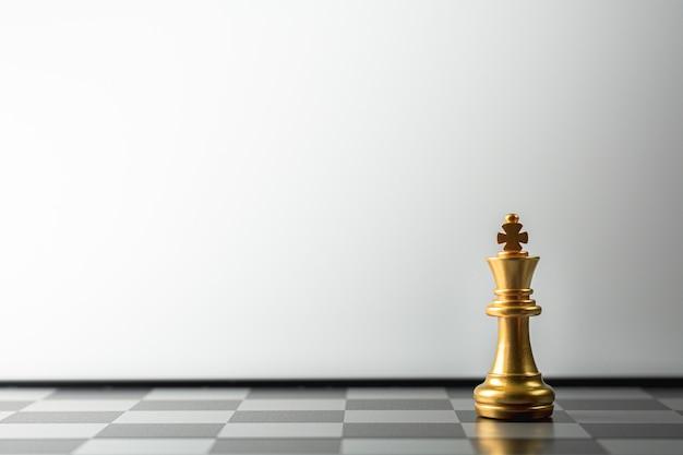 Einsames goldenes königschach, das auf schachbrett steht.