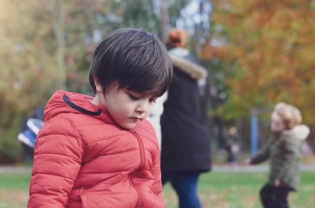Einsames kind des emotionalen porträts, das allein im spielplatz sitzt, trauriger junge, der allein am park, unglückliches kind mit dem denkenden gesicht schaut unten mit traurigem gesicht, verdorbenes kinderkonzept spielt