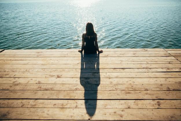 Einsames mädchen, das auf dem pier im sommer sitzt