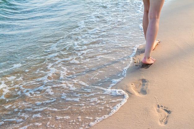 Einsames mädchen, das auf den sand mit abdrücken mit welle geht
