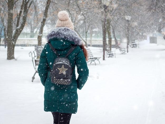 Einsames mädchen, das im park während des schneefalls geht