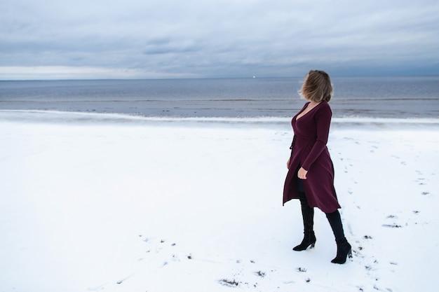 Einsames mädchen im burgunderfarbenen kleid auf dem hintergrund des meeres. porträt einer frau auf see, windiges wetter, kaltes atmosphärisches bild.
