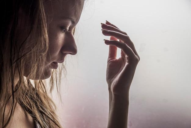 Einsames mädchen in der nähe von fenster über etwas denken. traurige frau sucht den regen, der durch ein fenster zu hause fällt