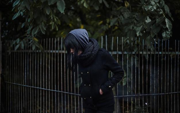 Einsames mädchen in einem schwarzen mantel, in einem brunette, in einer krise, in einer einsamkeit