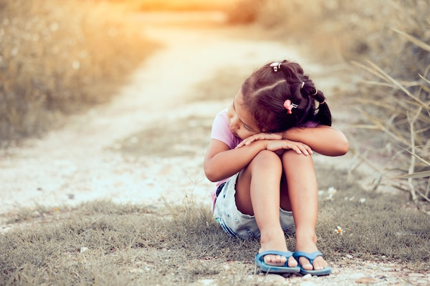 Einsames und trauriges kleines mädchen, das im park im weinlesefarbton sitzt