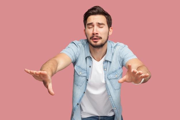 Einsamkeit und blindheit. porträt eines jungen mannes mit verlorener sorge in blauem freizeithemd, der mit geschlossenen augen steht und versucht, etwas zu berühren oder zu finden. indoor-studioaufnahme, isoliert auf rosa hintergrund.