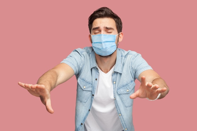 Einsamkeit und blindheit. porträt eines verlorenen sorgenmannes mit chirurgischer medizinischer maske in blauem hemd, der mit geschlossenen augen steht und versucht, etwas zu berühren oder zu finden. innenaufnahme, isoliert auf rosa hintergrund.