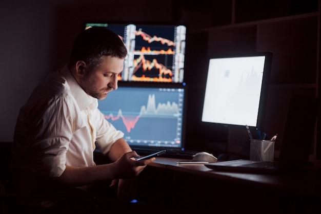 Einsatz moderner technologien bei der arbeit. junger geschäftsmann, der auf digitalem tablett beim sitzen am schreibtisch im kreativen büro arbeitet.