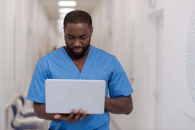 Einsatz von technologie für die medizin. charmant war ein afroamerikanischer arzt, der im krankenhaus stand, während er arbeitete und einen laptop benutzte