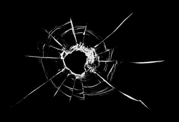 Einschussloch im glas. auf schwarzem hintergrund isoliert.