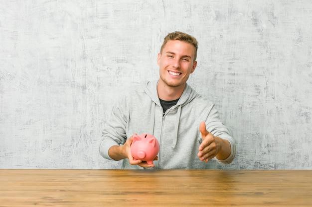 Einsparungsgeld des jungen mannes mit einem sparschwein, das hand an der kamera in der grußgeste ausdehnt.