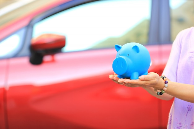 Einsparungsgeld und darlehen für autokonzept, junge frau, die blaues sparschwein mit stellung am autoparken, autogeschäft hält