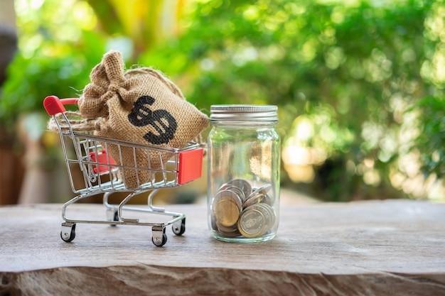 Einsparungsgeldkonzept des sammelns von münzen (thailändisches geld) in einem warenkorb