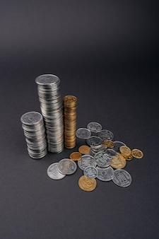 Einsparungsgeldmünzenstapel ragen dunkle oberfläche hoch
