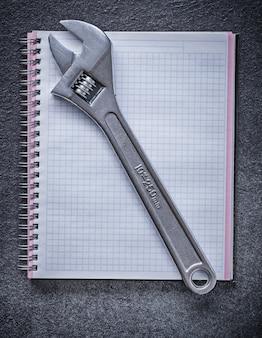 Einstellbares schraubenschlüssel-notizbuch auf schwarzem hintergrundkonstruktionskonzept
