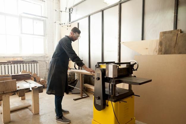 Einstieg in die arbeitskleidung, die holz auf stationärem elektrowerkzeug verarbeitet