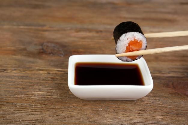 Eintauchen von rolle in sauce auf holztisch