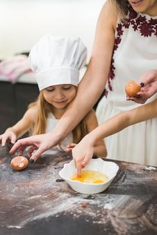 Eintauchender finger des kleinen mädchens im ei während mutter, die lebensmittel auf unordentlicher küchenarbeitsplatte zubereitet
