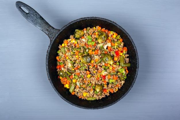 Eintopf mit verschiedenem gemüse und fleisch in einer pfanne auf grauem hintergrund, draufsicht.