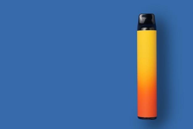 Einweg-e-zigarette in gelber farbverlaufsfarbe auf blauem, isoliertem hintergrund. das konzept des modernen rauchens, dampfens und nikotins. ansicht von oben