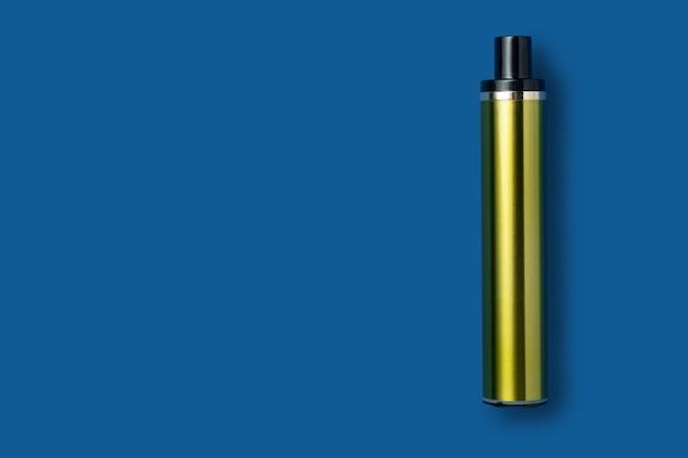 Einweg-e-zigarette in grüner metallfarbe auf blauem, isoliertem hintergrund. das konzept des modernen rauchens, dampfens und nikotins. ansicht von oben