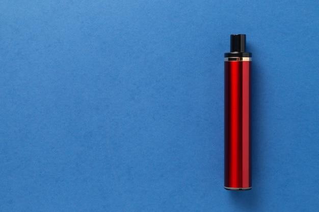 Einweg-e-zigarette in roter farbe auf blauem, isoliertem hintergrund. das konzept des modernen rauchens, dampfens und nikotins. ansicht von oben