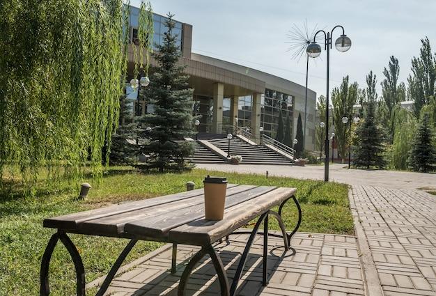Einweg-kaffeetasse aus braunem papier. steht im sommer auf einer bank in der natur.